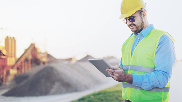 man in a hardhat reading a report