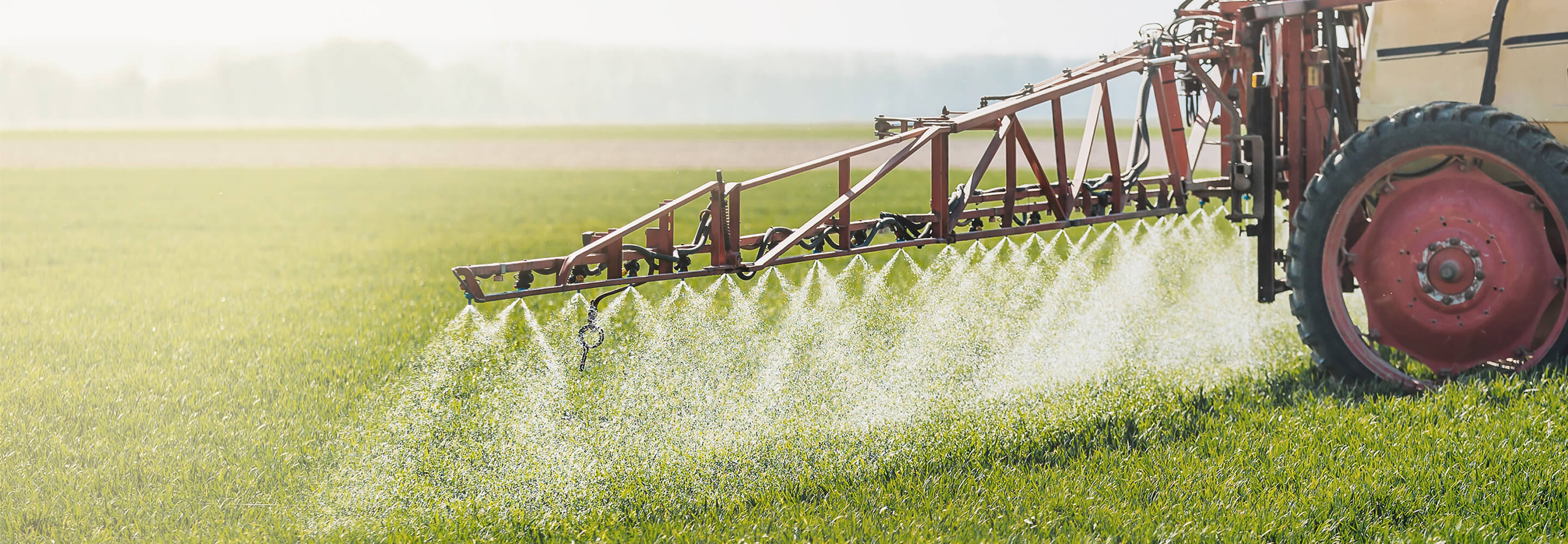Green pasture being sprayed with chemicals