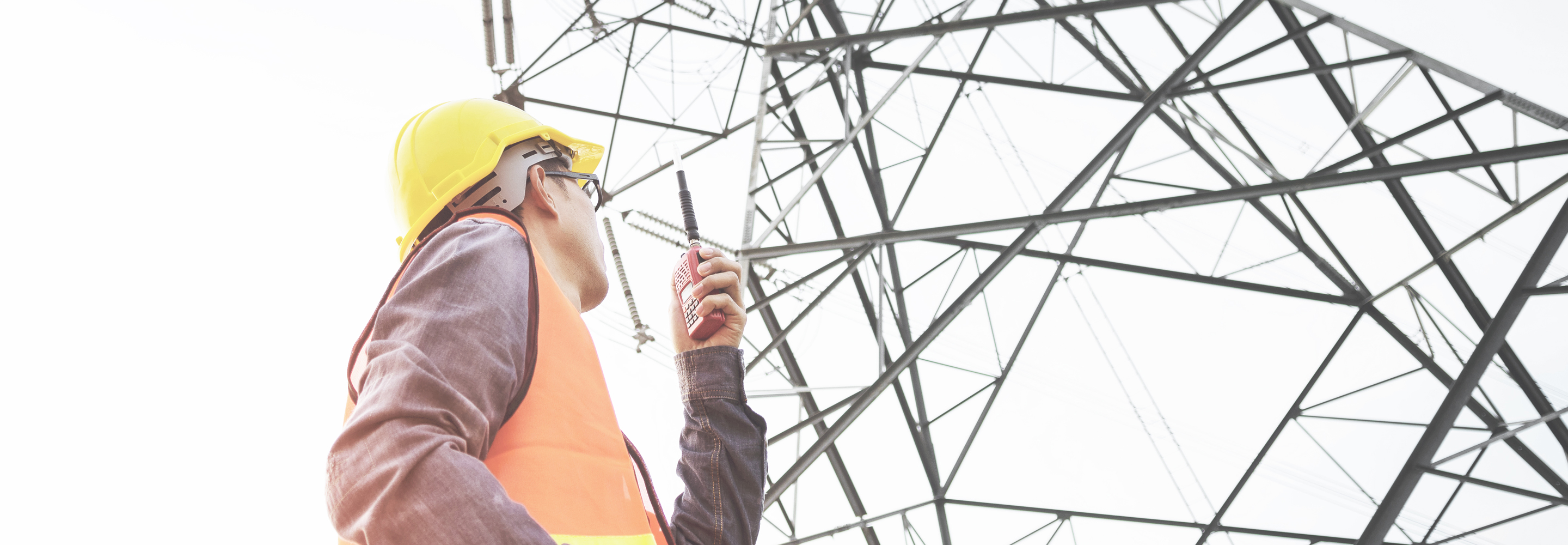 man with hard hat looking up at transmission tower