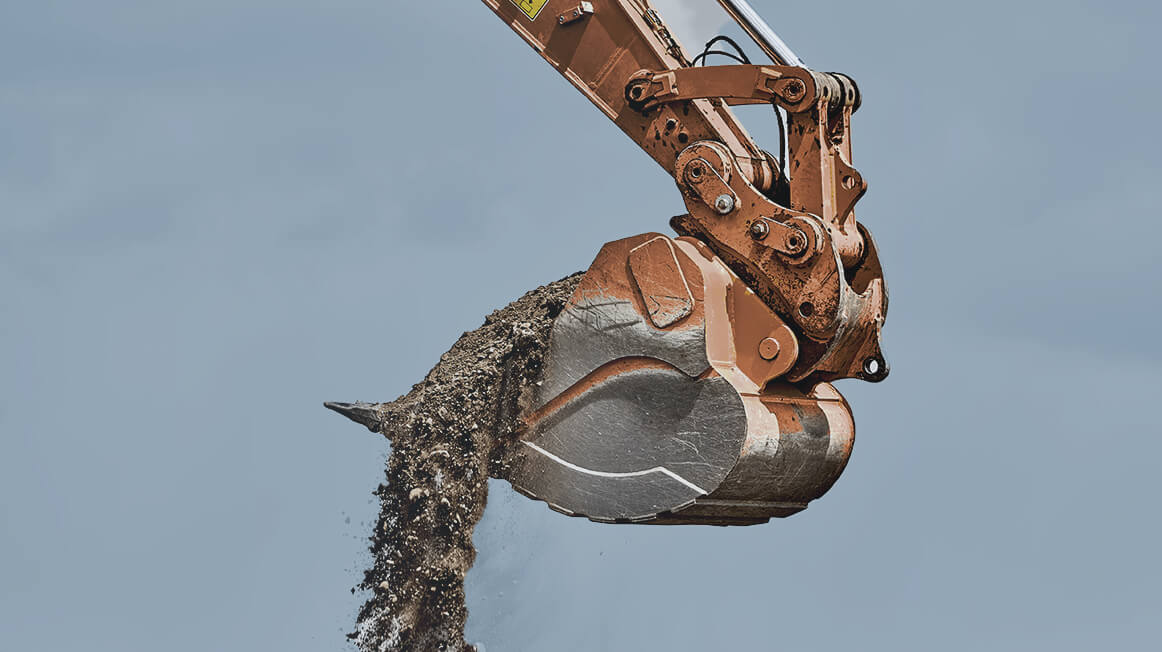 excavator lifting up dirt for mining