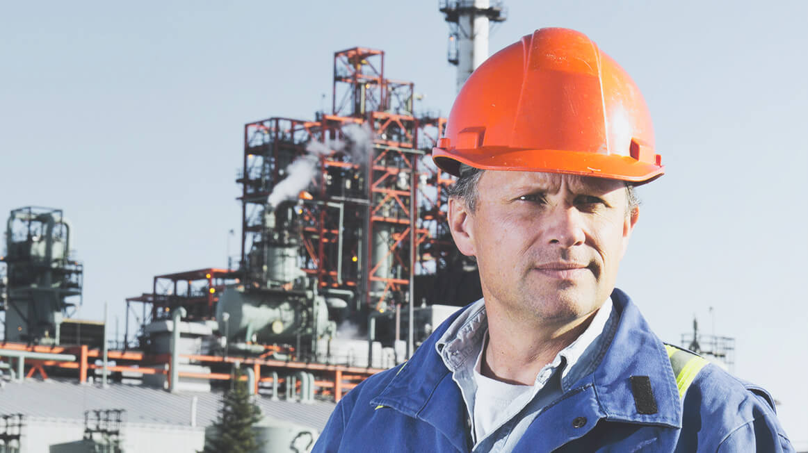 refinery worker with hard hat in front of oil refinery