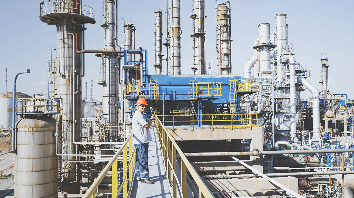worker on catwalk at oil refinery