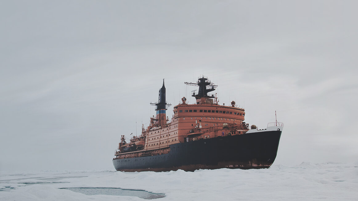 large ship sailing through icy water
