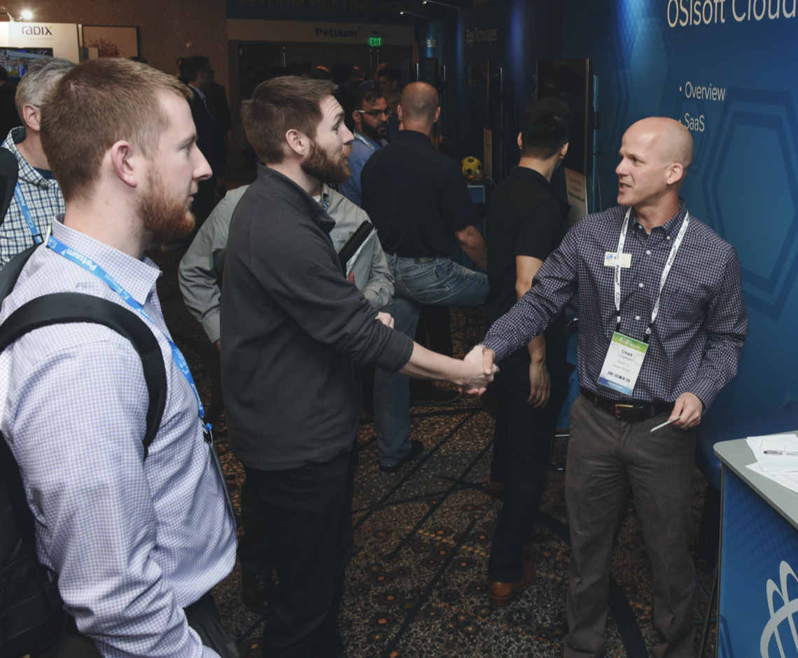 three people meeting at an OSIsoft Partner event