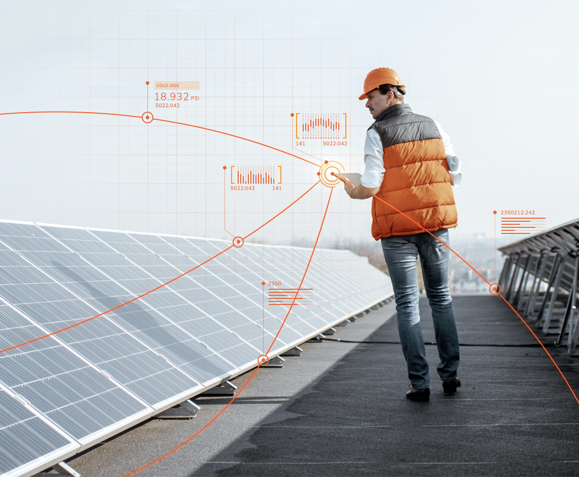engineer in orange vest and hard hat walking next to solar panel