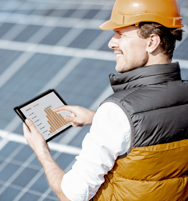 person with a hardhat with a chart on a tablet at a solar farm