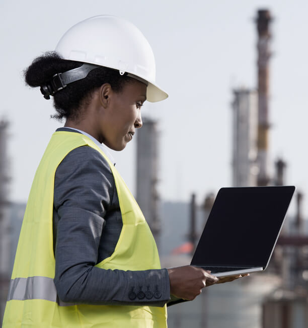 woman in a hard hat with a laptop with oil plant in the background