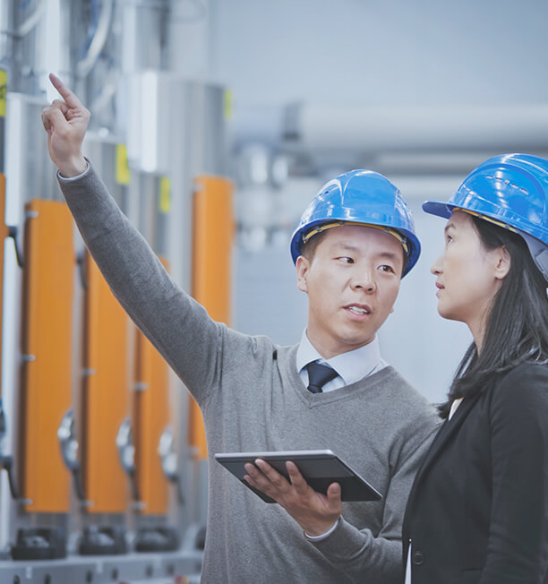 two people in hard hats at a plant one person explaining something with tablet in hand