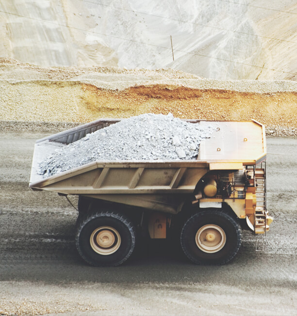 mining truck on a road with bed filled with dirt