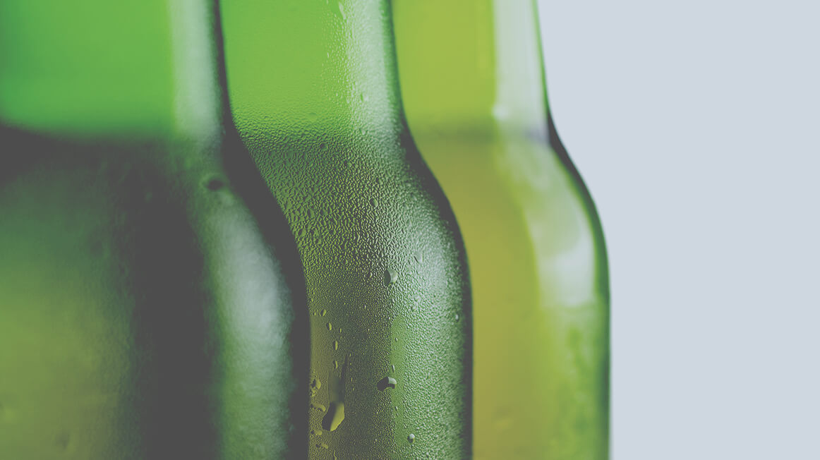 close up of green glass beer bottles