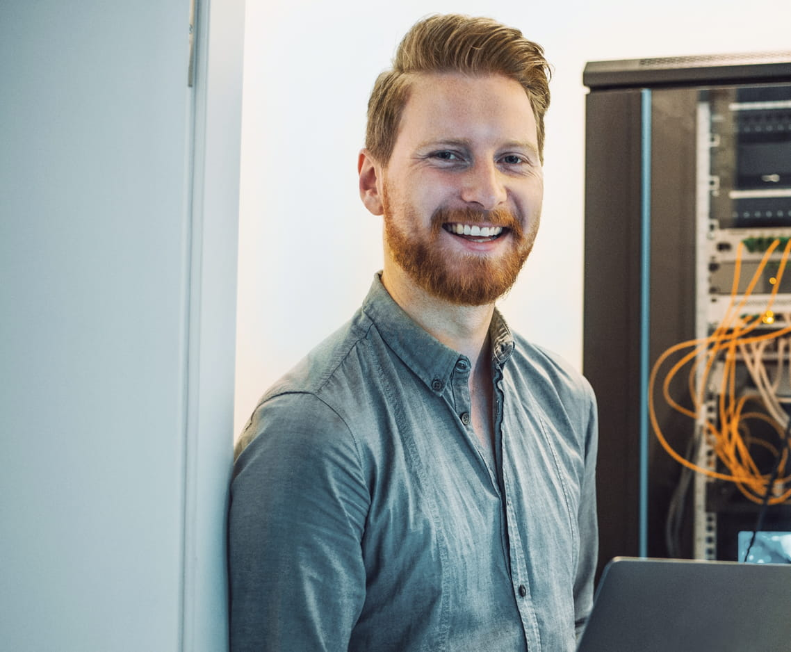 happy IT person in front of a networking rack
